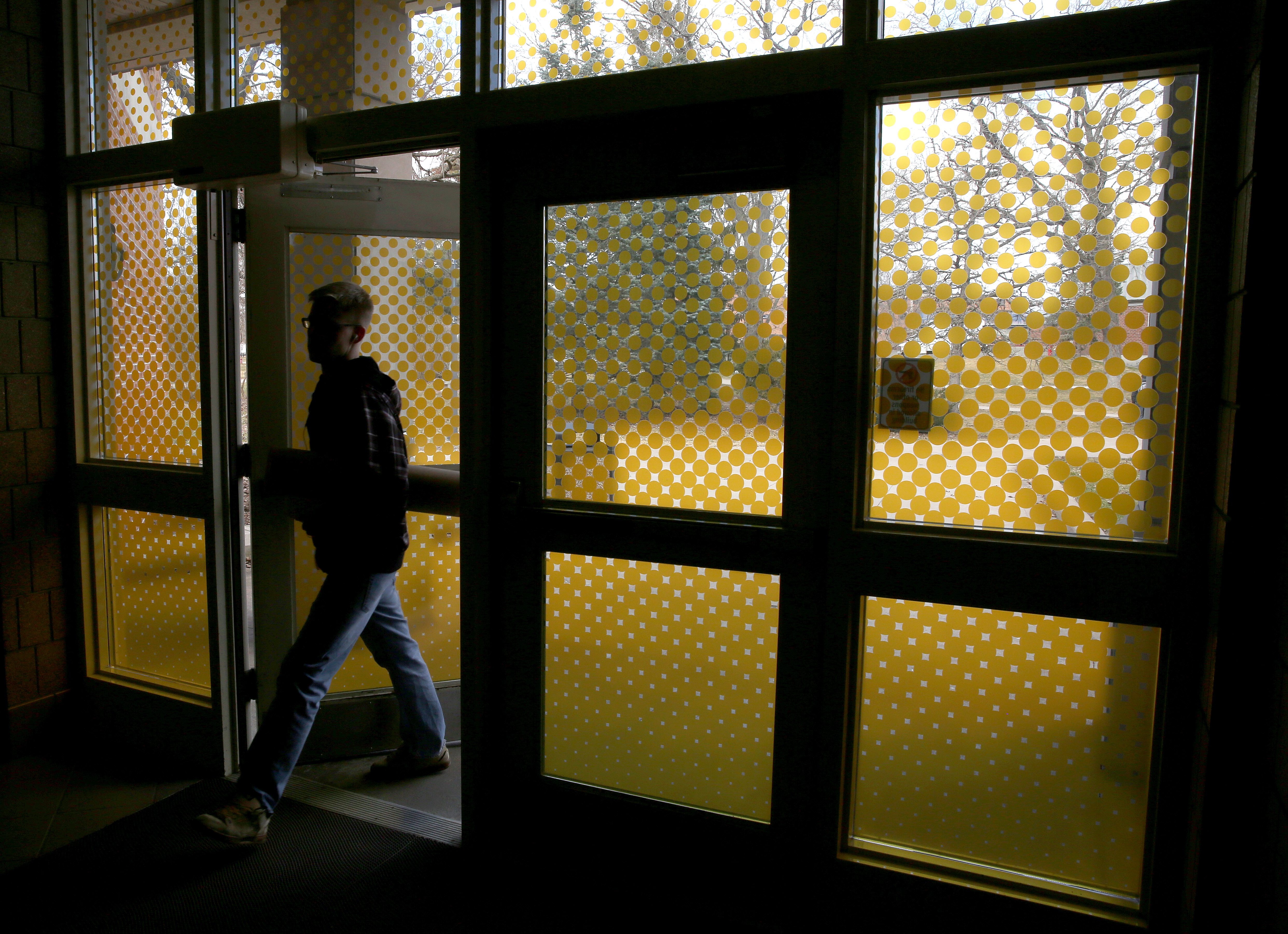 Students walking on campus can be seen through a vinyl graphic that the School of Art and Design has applied to the exterior doors of Applied Arts and Micheels Hall Thursday, March 26, 2015. (UW-Stout photo by Brett T. Roseman)